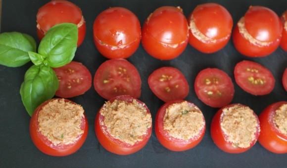 Tomaten gefüllt mit Mandeltartar, vegan, auf Brett angerichtet und Basilikum dekoriert