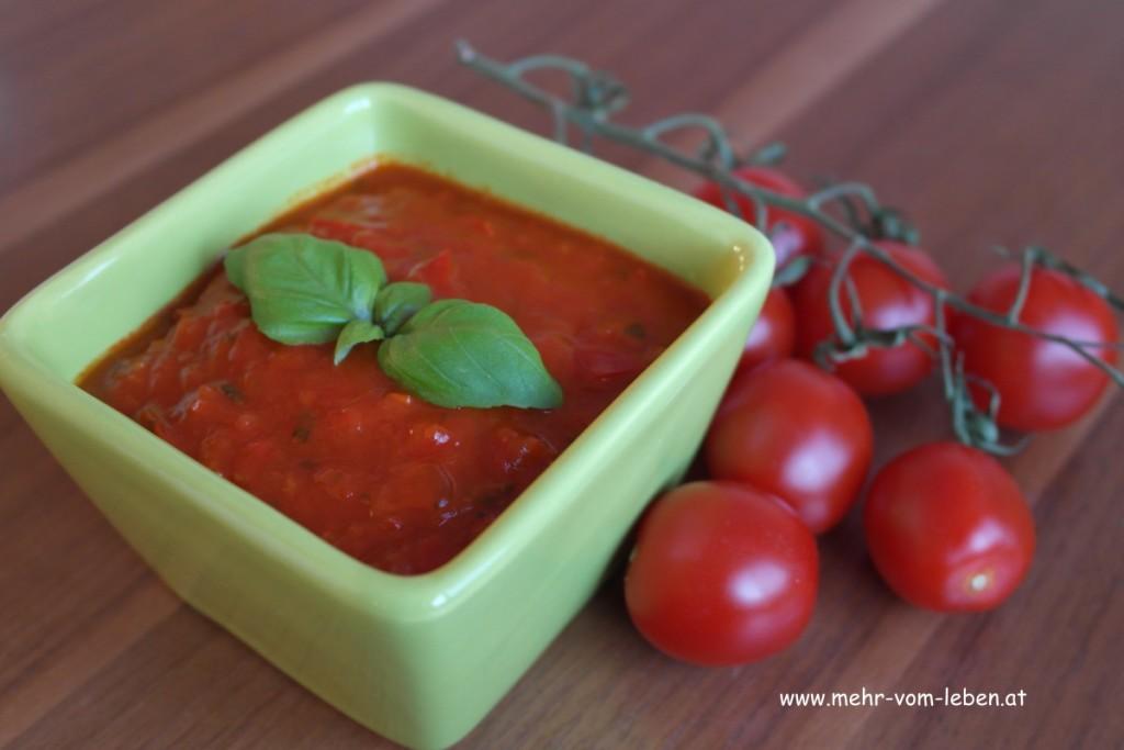 Tomatensauce vegan in Schüssel und Cherrytomaten auf Rispe